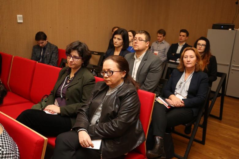 zdjęcie: kilka osob siedzi na czerwonych krzesłach
